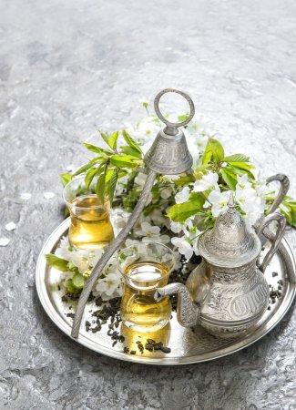 Tea glasses and pot. Oriental silver tableware. Flowers decorati