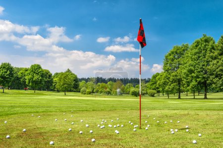 Golf field and cloudy blue sky. Spring landscape with grass and