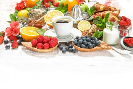 Photo for Healthy breakfast table with coffee, croissants, muesli, fresh berries, fruits orange, apple, yogurt, honey, milk. Organic food concept - Royalty Free Image