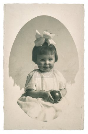 Old family photo portrait of little girl with toy ball