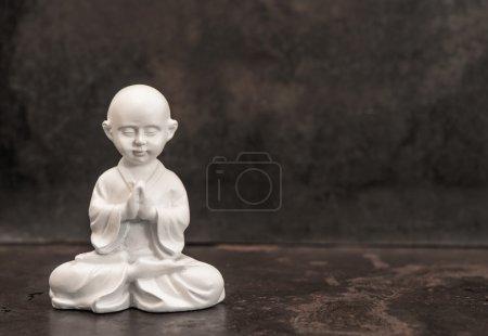 Photo pour Bouddha priant. Statue de moine blanc sur fond sombre. Concept de méditation - image libre de droit