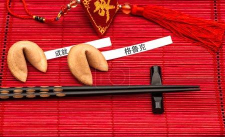 Photo pour Porte-bonheur du nouvel an chinois, épigrammes et baguettes noirs sur la natte de bambou rouge. Exemple de texte réussite et le bonheur - image libre de droit