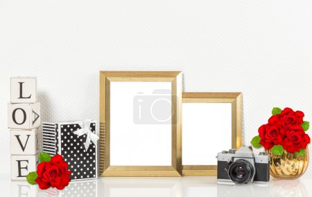 Photo for Golden picture frames, red rose flowers, vintage camera. Retro style decorations with space for your photo - Royalty Free Image