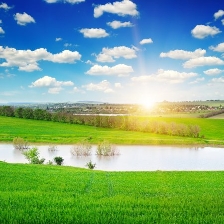 green field, lake and sunrise