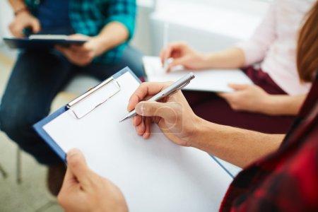 Photo pour Guy prend des notes pendant l'étude en groupe psychologique - image libre de droit