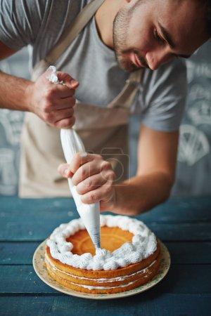 Baker decorating tasty cake