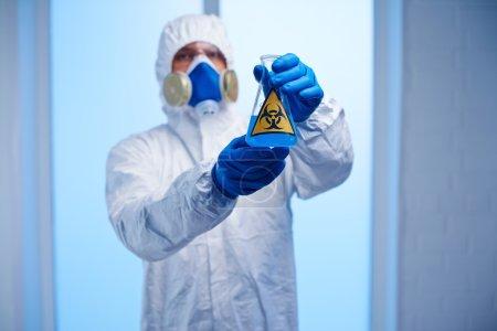 Photo pour Chimiste en général protecteur, respirateur et gants tenant la fiole avec du liquide toxique bleu - image libre de droit
