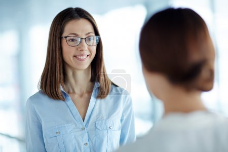 Photo for Smiling businesswoman listening to colleague - Royalty Free Image