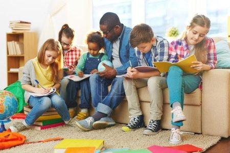 Photo pour Petits enfants Prendre des notes dans leurs copybooks à la leçon - image libre de droit
