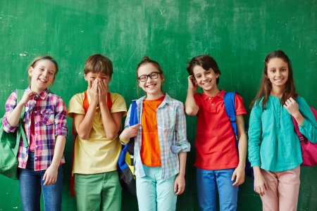 Photo for Happy pupils in colorful clothes against chalkboard - Royalty Free Image