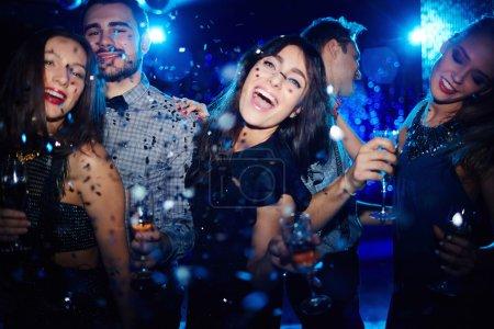 Photo pour Jeunes gens heureux dansant avec du champagne à la fête - image libre de droit