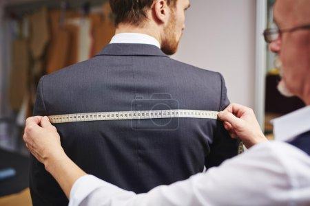 Photo pour Mature tailleur prendre des mesures de veste homme d'affaires - image libre de droit