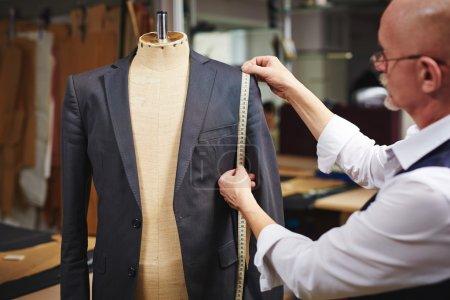 Photo pour Mature tailleur prendre des mesures de veste homme sur mannequin - image libre de droit