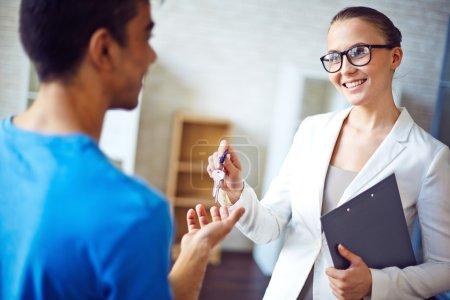 Photo pour Agent immobilier donnant sa clé de client de plat - image libre de droit
