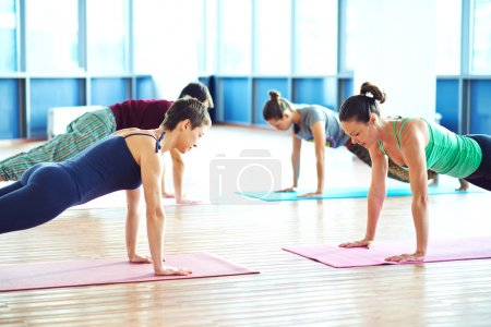 Photo pour Young People working out in bright gym - image libre de droit