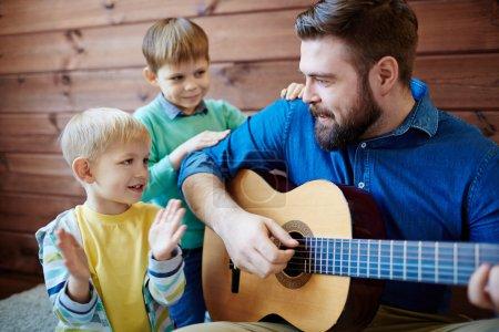 Photo pour Jeune homme jouant de la guitare avec deux fils à proximité - image libre de droit