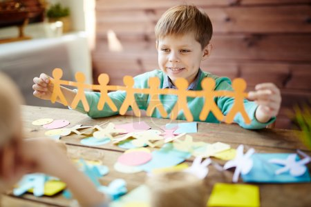 Photo for Happy boy showing orange paper figures - Royalty Free Image