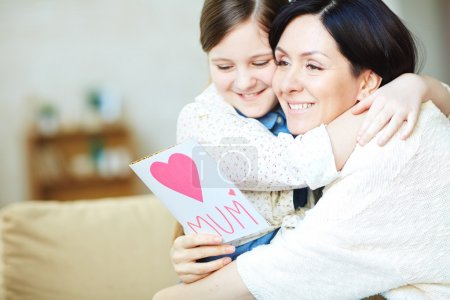Photo for Young woman with card and her daughter embracing - Royalty Free Image