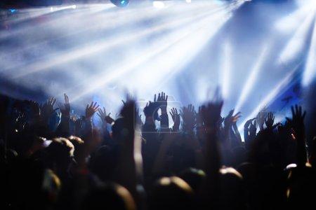 Photo pour Foule de fans extatiques avec les mains levées appréciant les chansons - image libre de droit