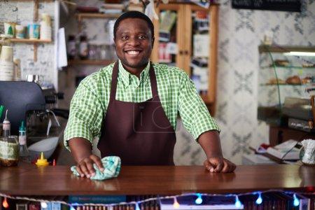 Photo pour Portrait d'un homme joyeux travaillant au comptoir du bar - image libre de droit
