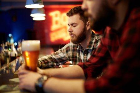 Photo pour Jeune homme avec son ami boire de la bière fraîche dans un pub - image libre de droit
