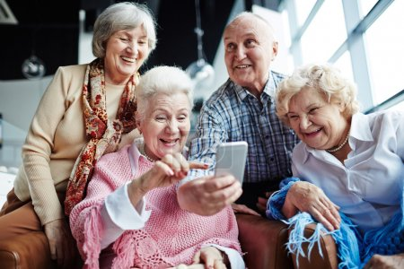 friendly seniors with smartphone