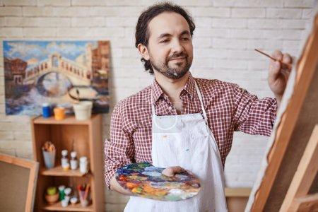 Male Artist painting in his art studio