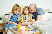 father and daughters with breakfast
