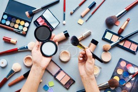 Photo pour Mains féminines tenant la poudre compacte avec des articles de beauté sur la table - image libre de droit