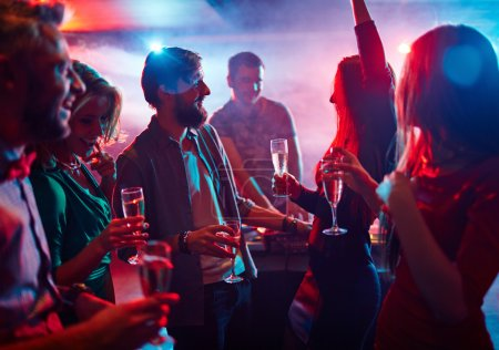 Photo pour Amis extatiques avec champagne dansant en boîte de nuit - image libre de droit