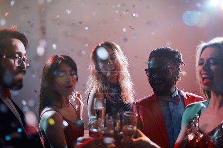 Photo pour Jeunes gens heureux dansant et grillage avec du champagne en fête - image libre de droit