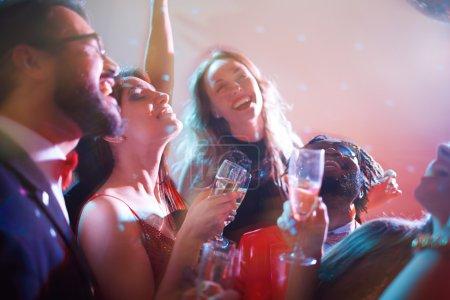 Photo pour Jeunes gens heureux dansant avec champagne à parti - image libre de droit