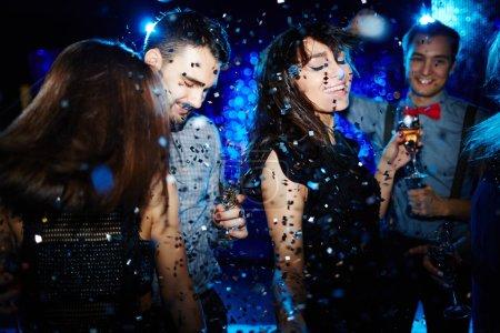 Photo pour Jeunes amis heureux dansant avec champagne à parti - image libre de droit