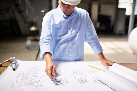 Photo pour Ingénieur moderne prenant des mesures de pièce de machine avec étriers sur croquis - image libre de droit