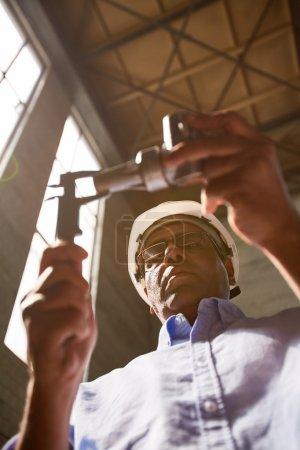 Photo pour Ingénieur moderne avec étriers prenant des mesures de pièce de machine - image libre de droit