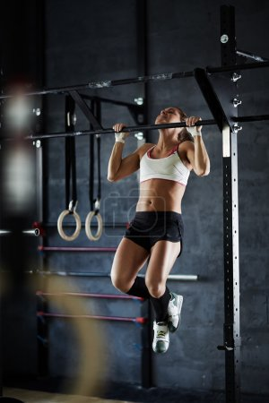 Photo for Young strong woman training on sport equipment in gym - Royalty Free Image