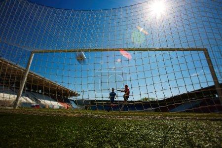 Photo pour Joueur de football donnant un coup de pied dans la porte - image libre de droit