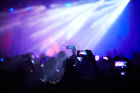 Photo pour Foule de fans extatiques avec mains surélevées bénéficiant d'enregistrement vidéo de chansons - image libre de droit