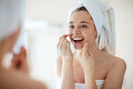 Photo pour Jeune femme soie dentaire devant le miroir - image libre de droit
