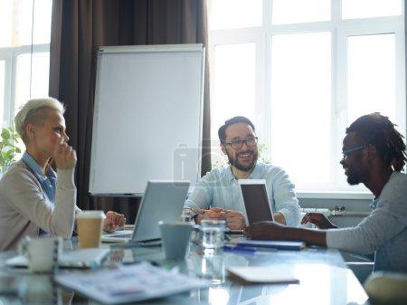 Foto de Gerente creativo hablando a sus trabajadores en reunión - Imagen libre de derechos