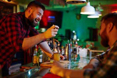 Photo pour Heureux barman clinking avec client dans bar - image libre de droit