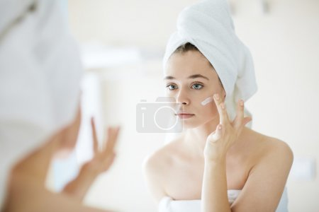 Photo for Pretty girl applying moisturizing cream in front of mirror - Royalty Free Image