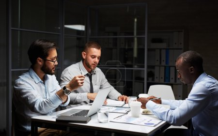 Three businessmen working late in office