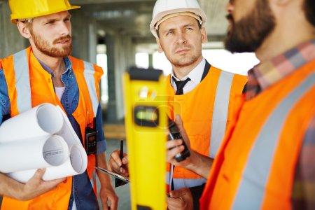 Photo pour Trois professionnels discutent lors d'une réunion sur le chantier - image libre de droit