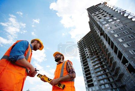 Modern inspectors talking by new building
