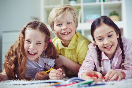Group of friendly children drawing in kindergarten...