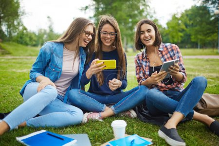 Photo for Girls with gadgets spending time in park - Royalty Free Image