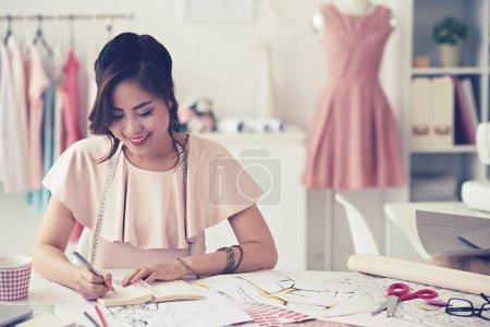 Photo pour Souriant charmante jeune femme couturière dessin croquis et motifs à la table - image libre de droit