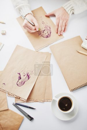 Designer drawing pictures on pages of notepad