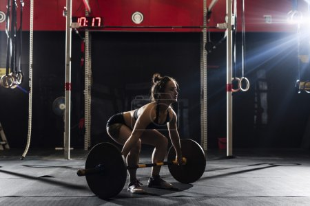 woman lifting heavy barbell